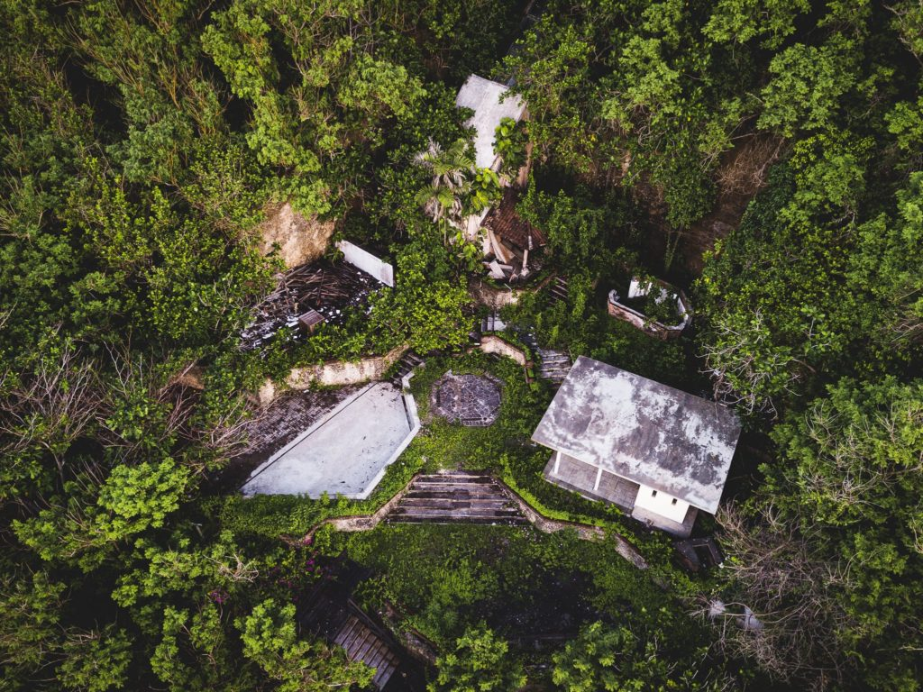 An aerial view of an abandoned tropical resort building on a cliffside