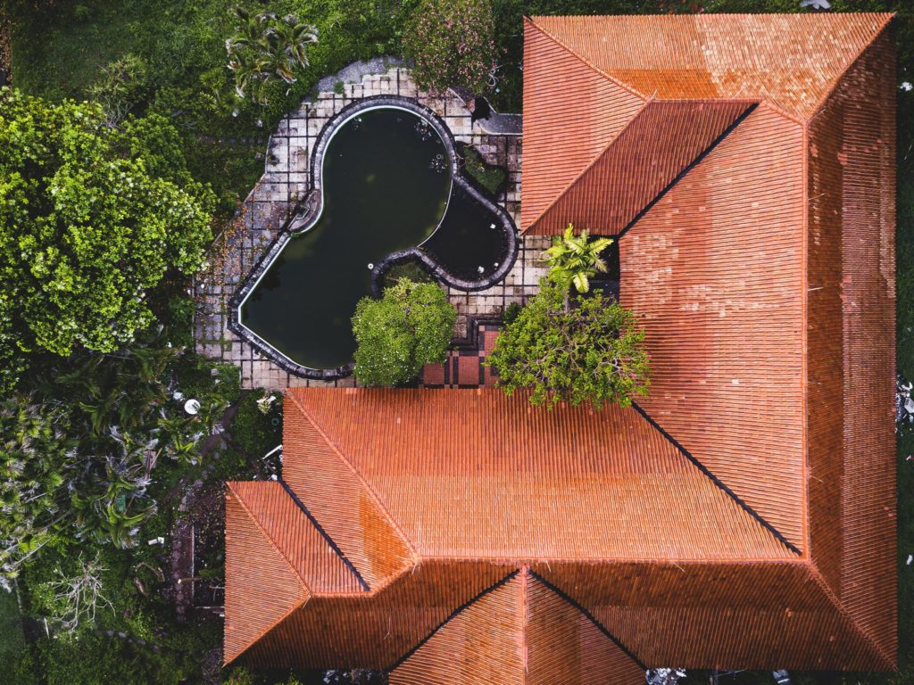 An aerial view of an abandoned resort building with a bright terracotta roof and a murky pool