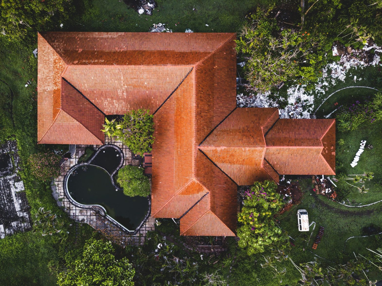 An aerial view of an abandoned resort building with a bright terracotta roof