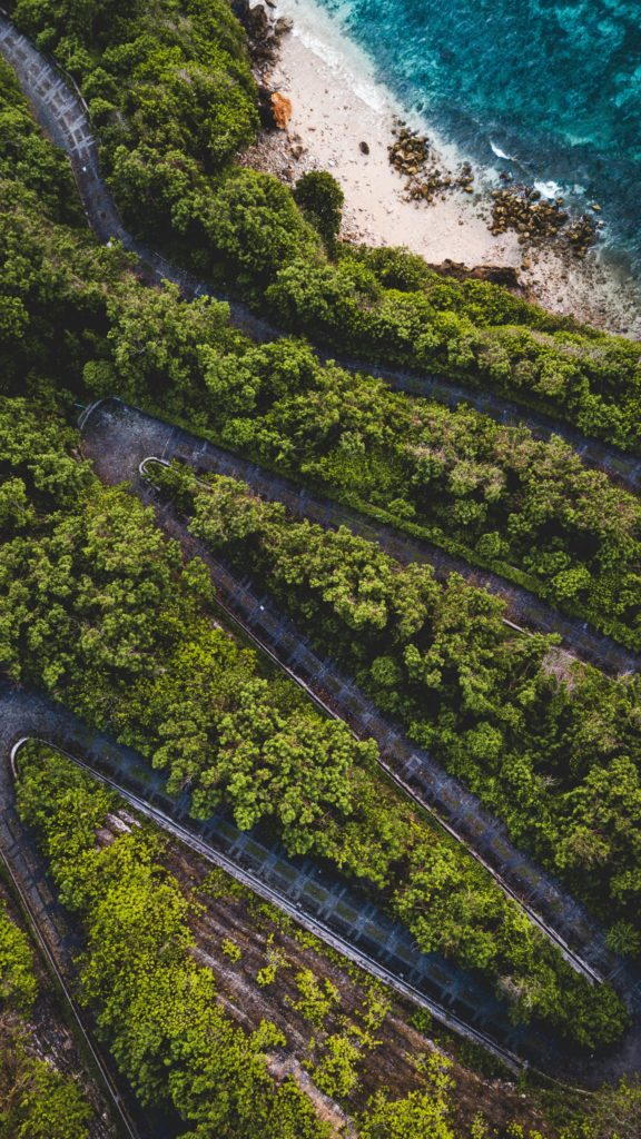 An aerial view of an old road winding wooden a cliffside to the beach
