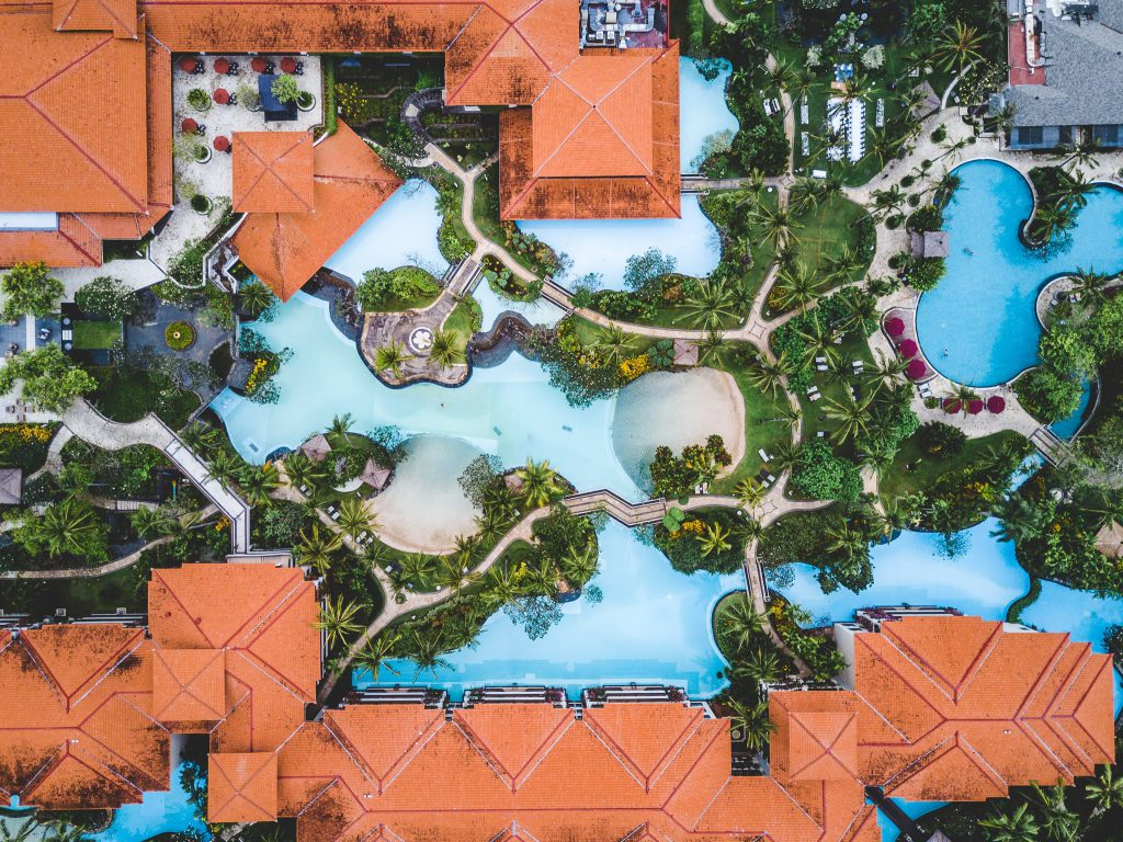 Aerial view of a tropical resort with pools and gardens around the buildings