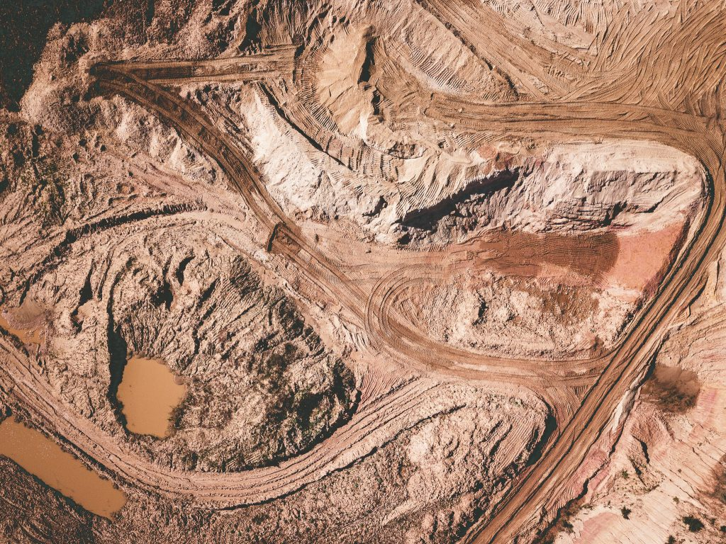 Aerial view of sand quarry earthworks showing a system of car tracks