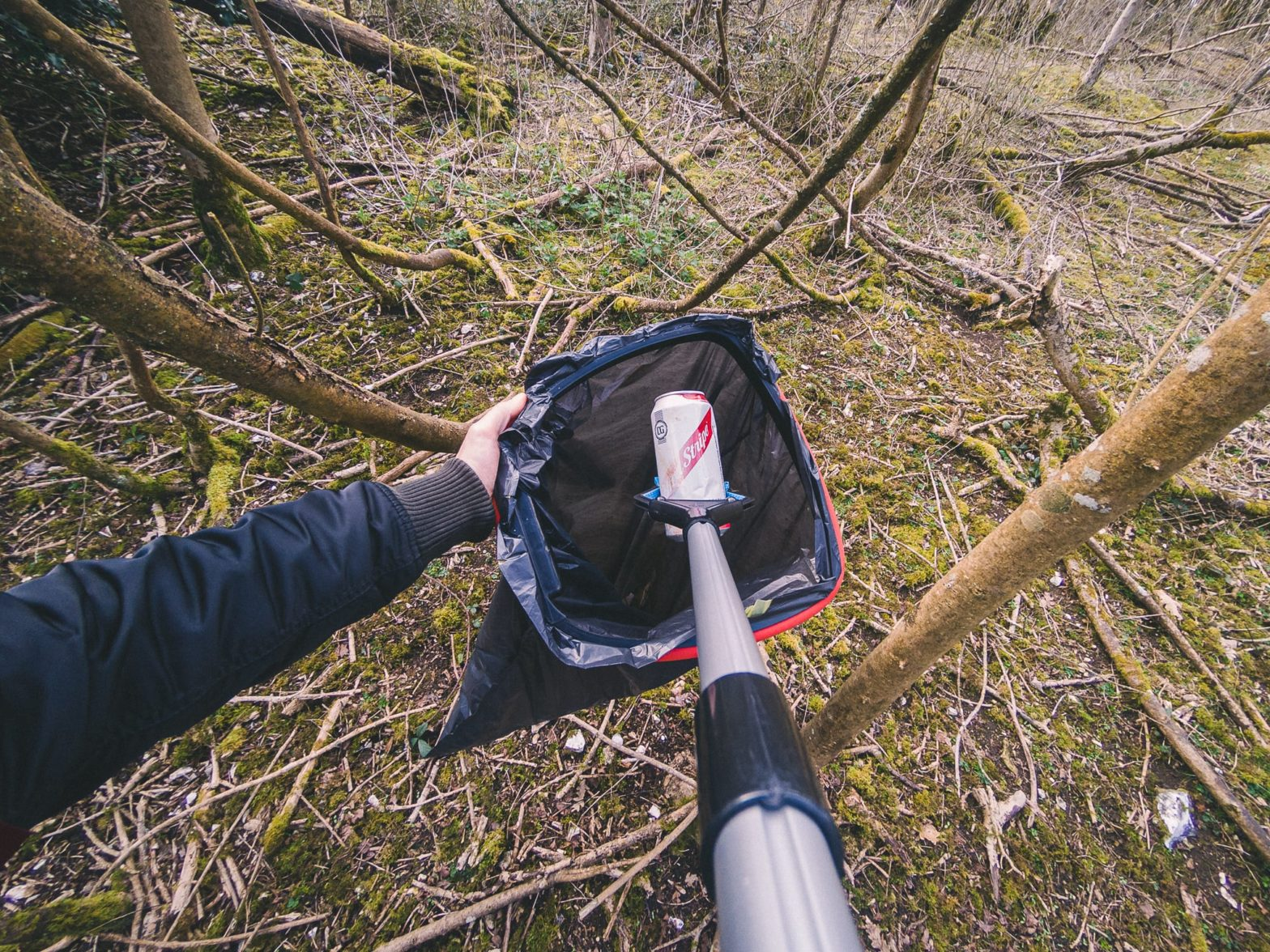 A discarded aluminium can in a forest being placed in a bag with a litter picker