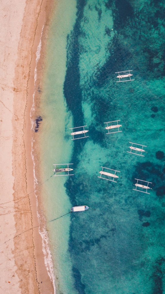 Aerial view of boats moored in the azure bay of the ocean
