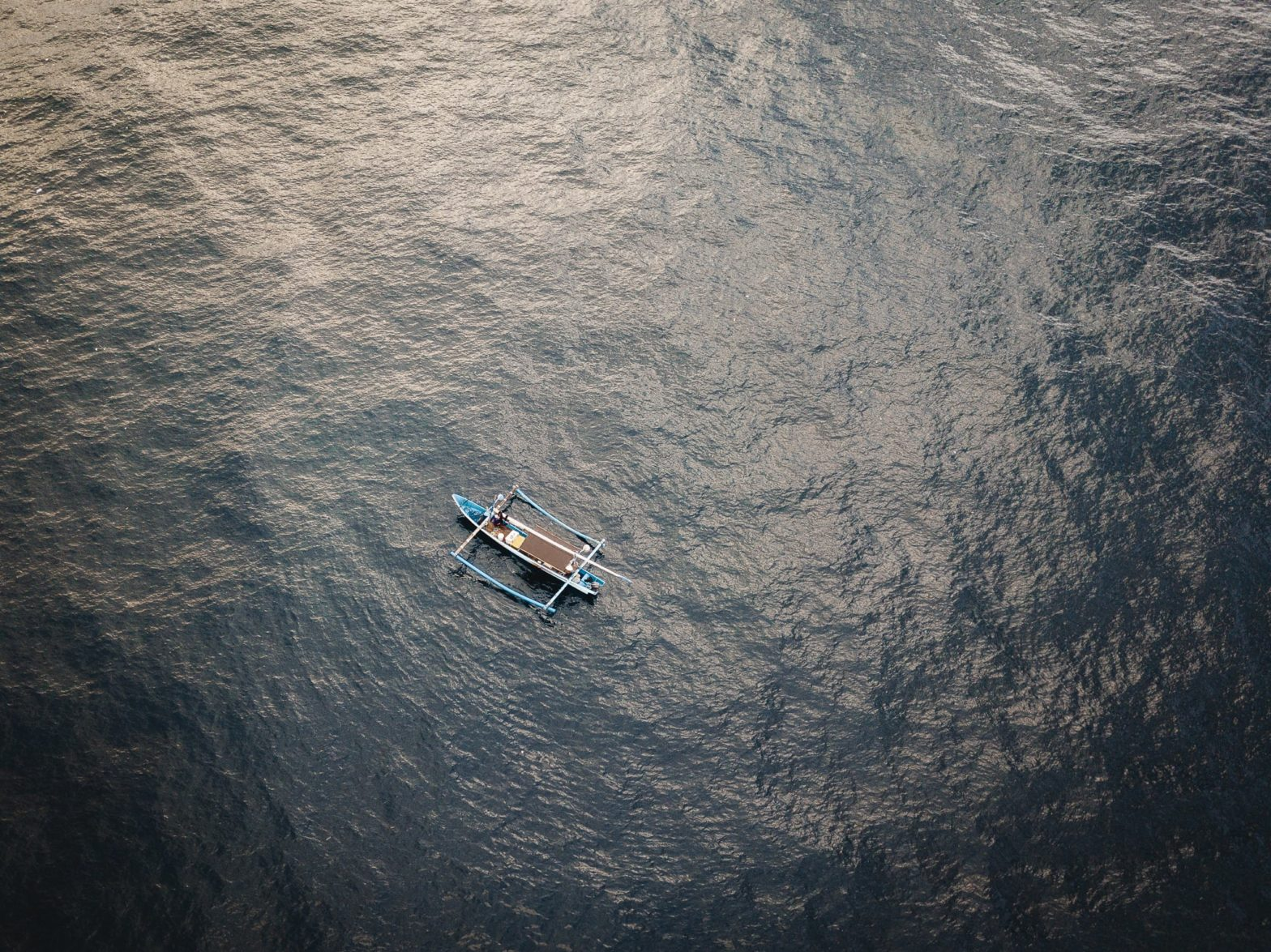 Aerial view of a fishing boat in the ocean early in the morning