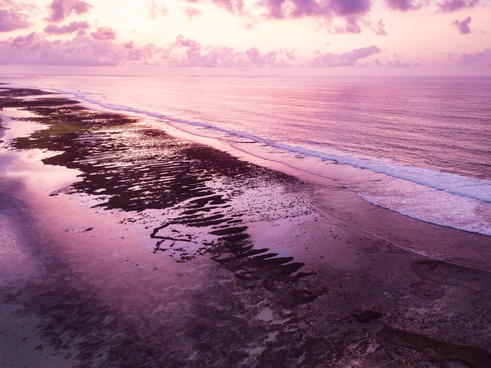 Aerial view of a coastal reef bathed in pink light just before sunrise