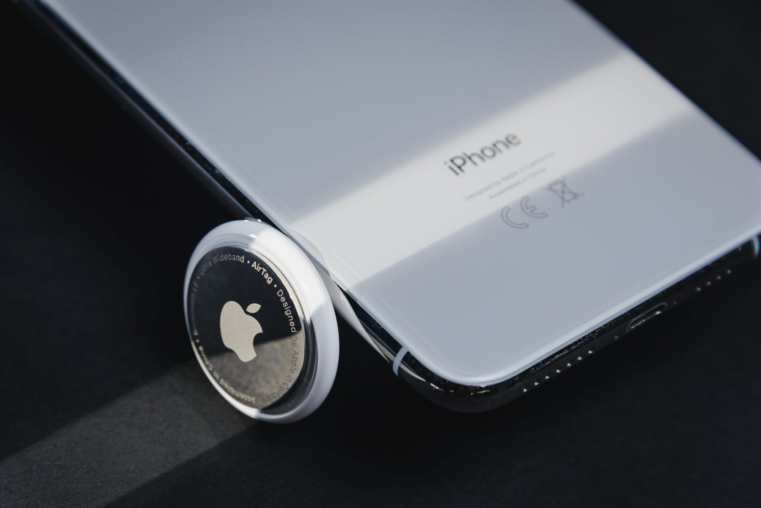 AirTag item tracker by Apple leaving agains an iPhone