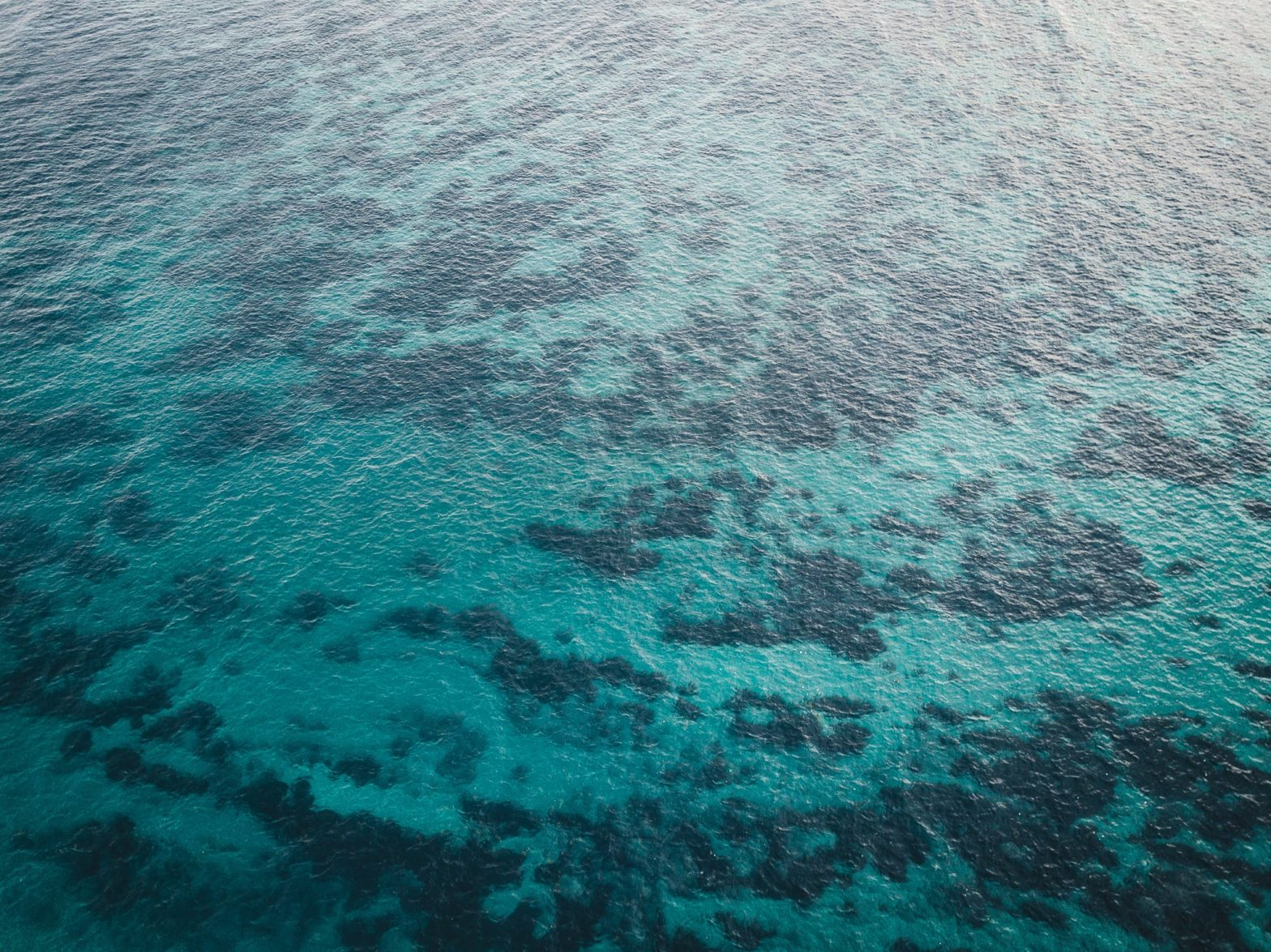 Aerial view of turquoise water in the bay with patches of darker seafloor visible