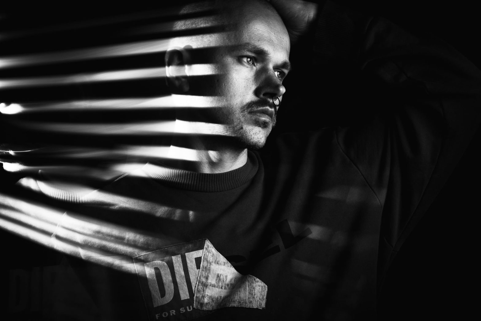 Low key black and white self portrait with a light trail on the left