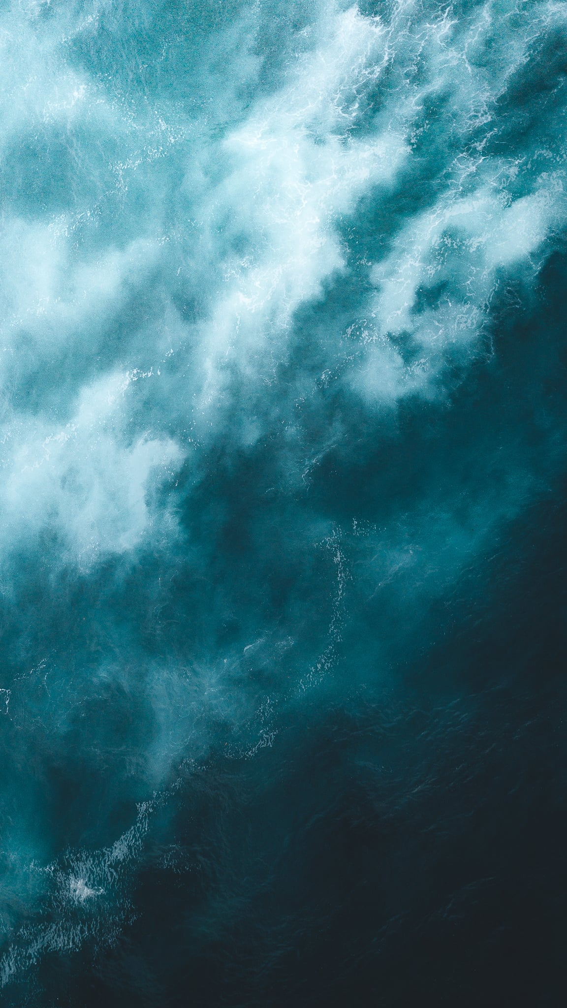 Aerial view of air bubbles trapped underwater forming abstract textures with top left part being bright and bottom right dark