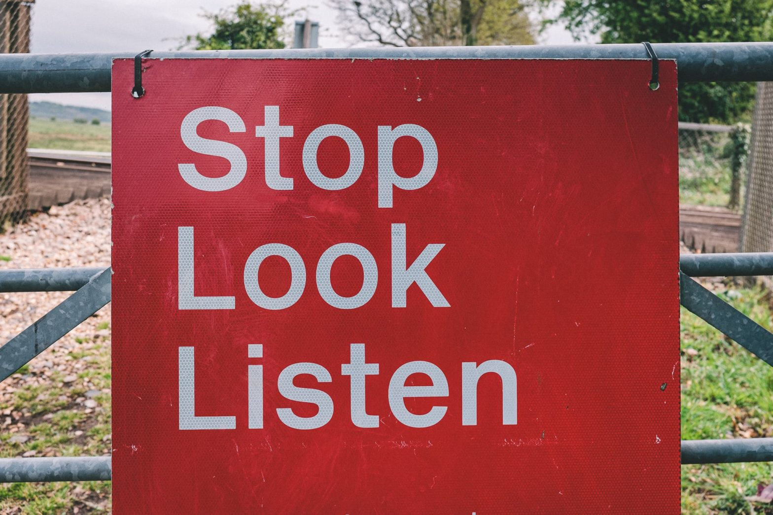 """A red warning sign at a railway crossing that says: """"Stop Look Listen"""""""