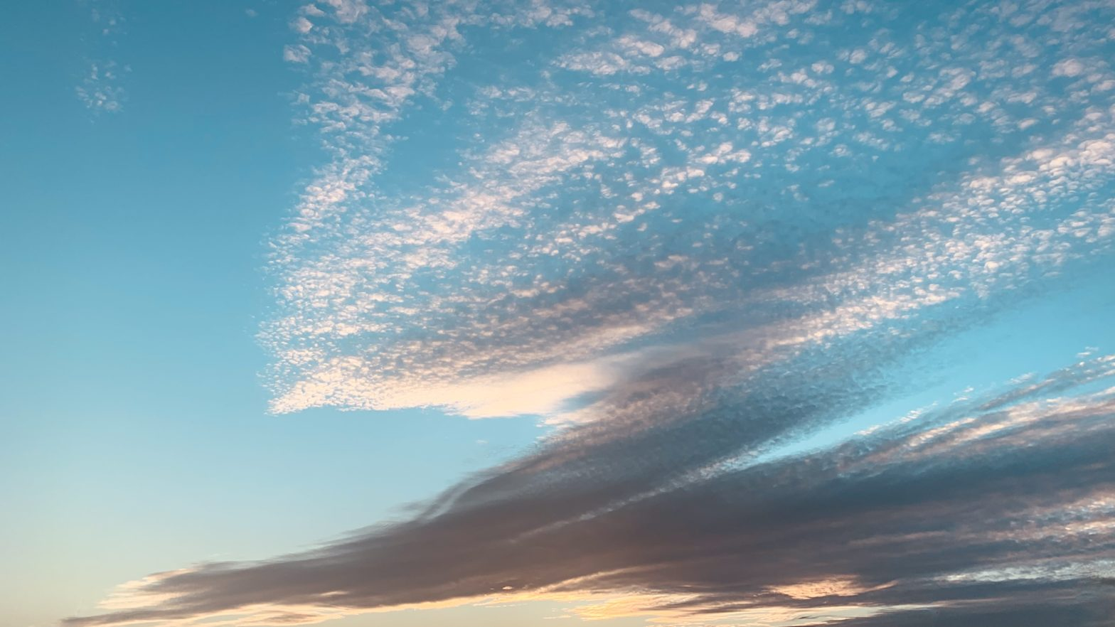 Scattered clouds just before sunset with clear sky visible to the left