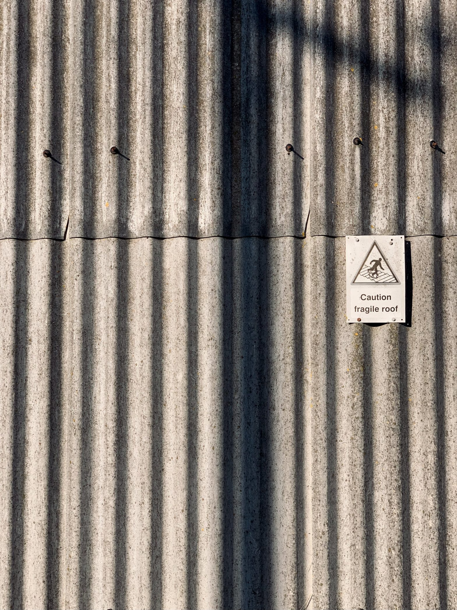 """Barn wall lined with corrugated sheets most likely made from cement with a sign that reads: """"Caution fragile roof"""". Vertical shadow is cast over the photo by a lamp post outside the frame."""