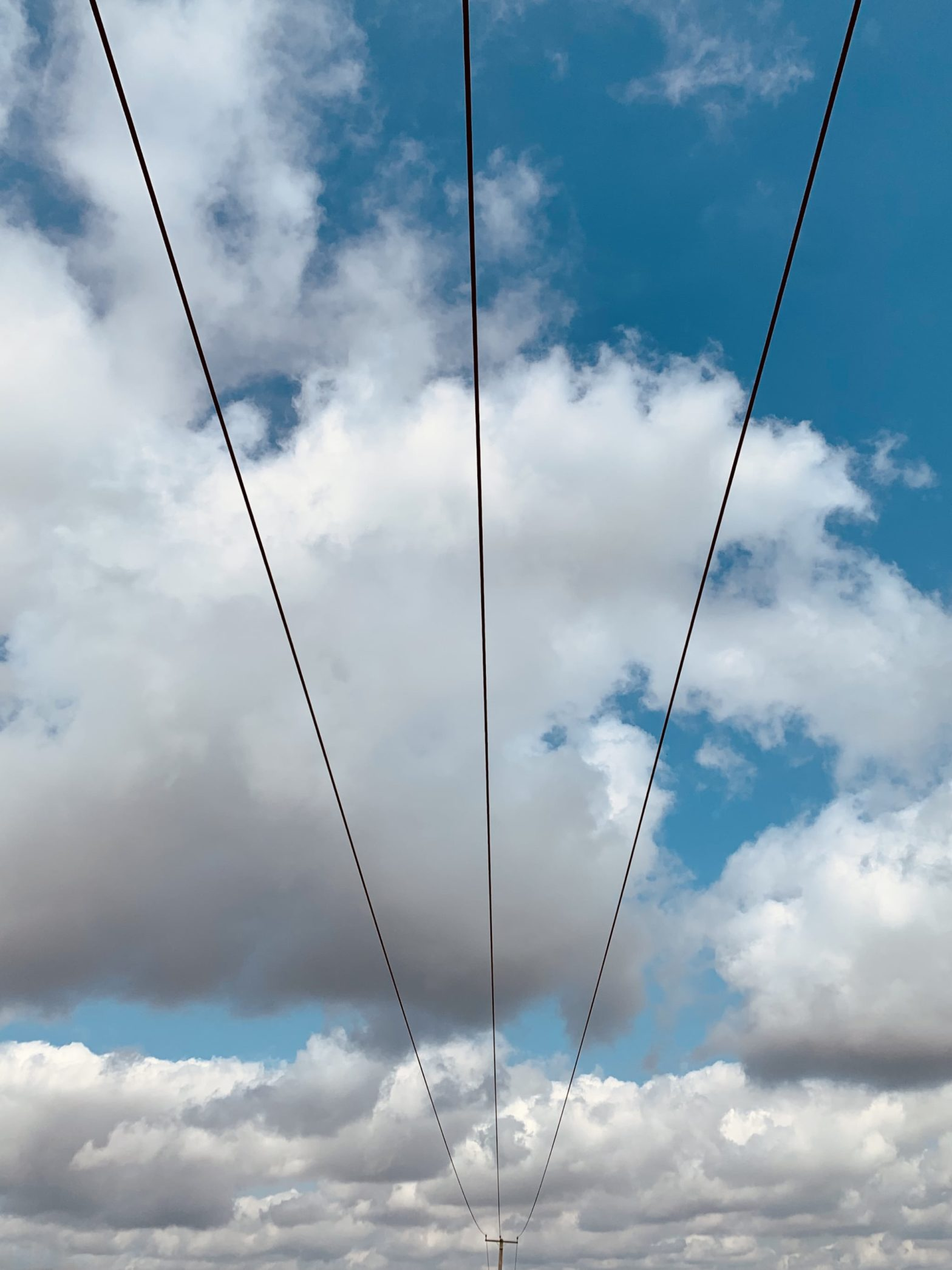 Power lines running in to the distance agains a blight blue sky with clouds