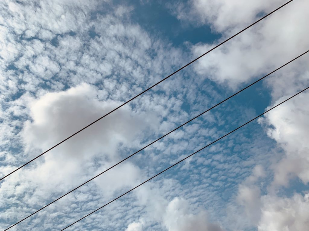 Clouds in the bright blue sky divided by 3 power lines running diagonally from bottom left to top right