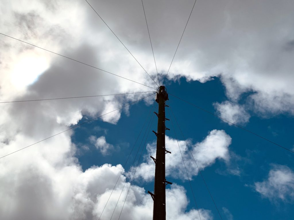 Telephone pole agains a backdrop of a cloudy sky at noon